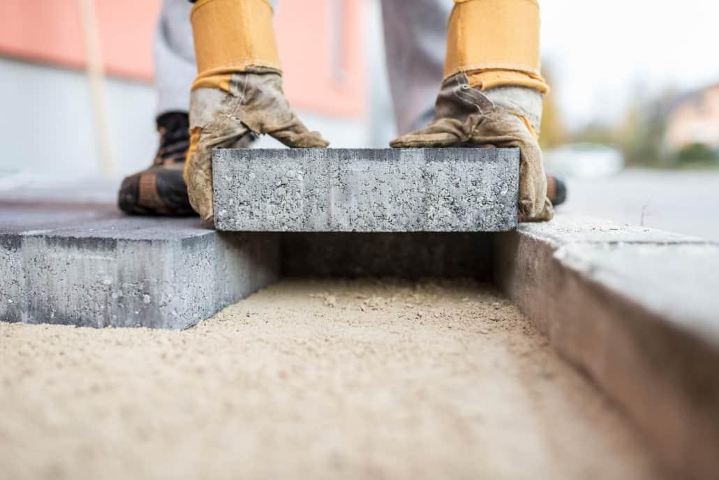 Workman laying exterior paving stones