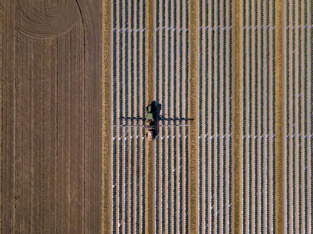 Straight down view of tractor spraying chemical fertilizer or pe